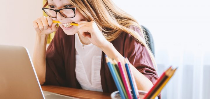 student near laptop with the pencil