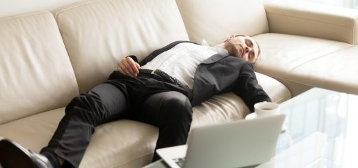 Man laying on the sofa near laptop