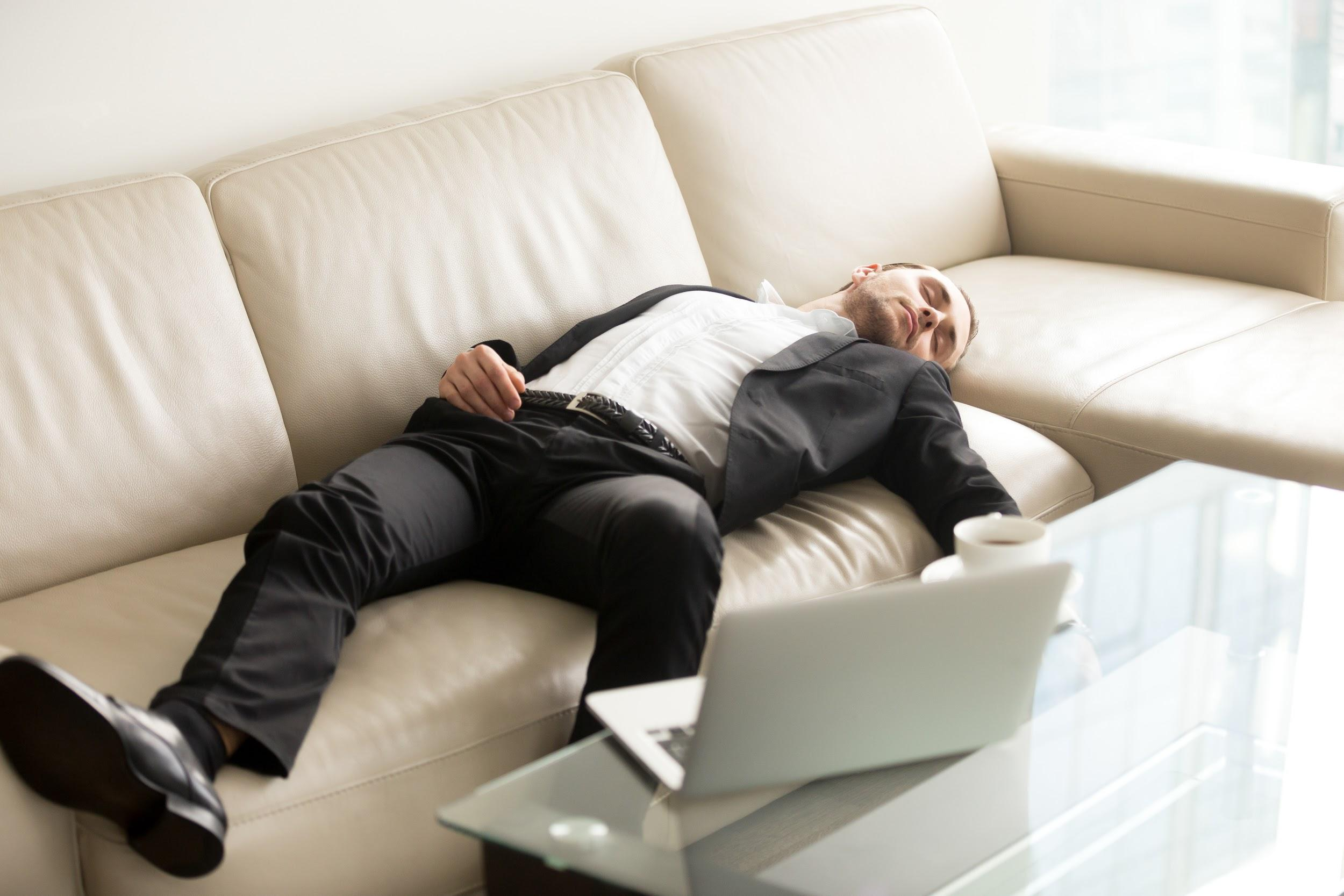 Man laying on the sofa near laptop